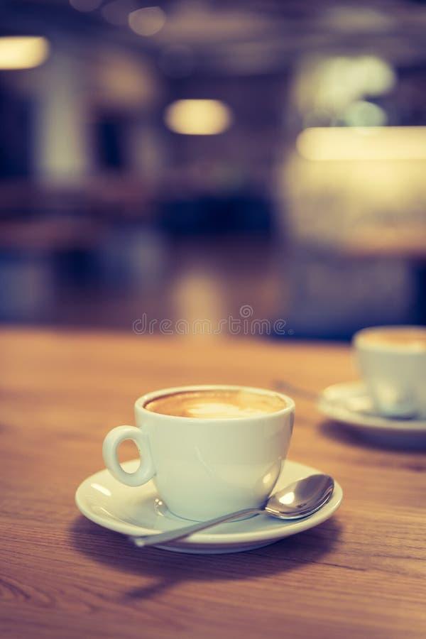 Schale italienischer Cappuccino in einem café, Morgen Café im undeutlichen Hintergrund stockbilder