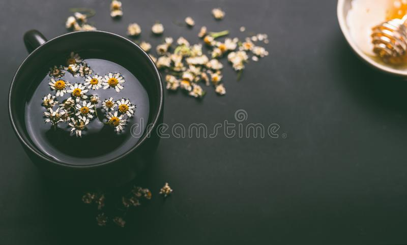 Schale Kräuterkamillentee mit getrockneten Kamillenblumen und -honig auf dunklem Hintergrund, Draufsicht Beheben Sie, um eine bre lizenzfreies stockbild