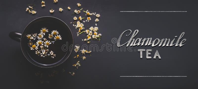 Schale Kräuterkamillentee mit getrockneten Kamillenblumen und -text auf dunklem Hintergrund, Draufsicht Beheben Sie, um eine brei stockfoto