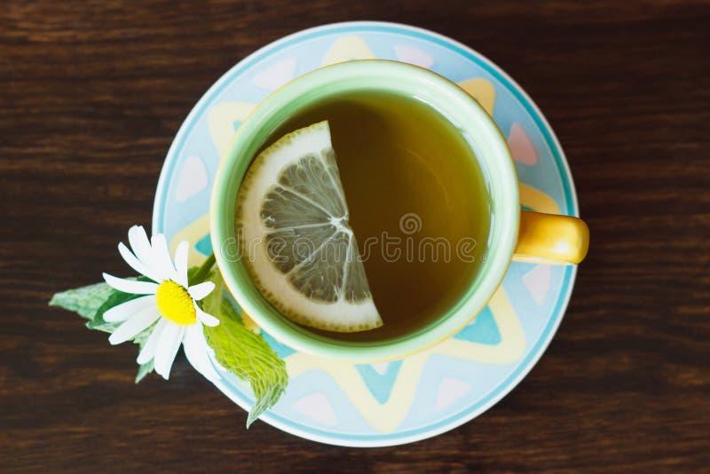 Schale Kräutertee mit Kamille und tadellosen Blättern auf dem hölzernen Hintergrund lizenzfreies stockbild