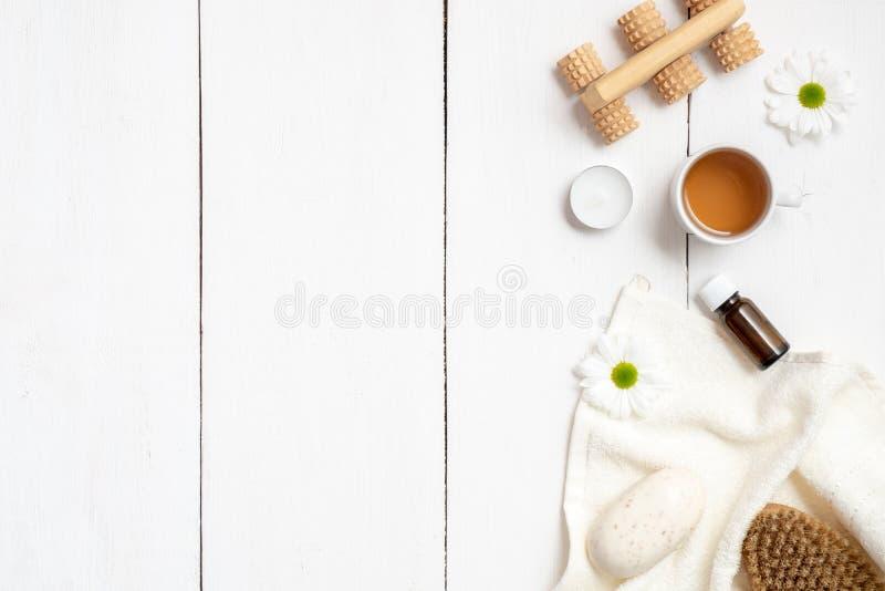 Schale Kräutertee, Tuch, Seife, ätherisches Öl und masseger auf weißem Holztisch Fahnenmodell für Schönheitssalon, Gesundheitswes lizenzfreies stockbild