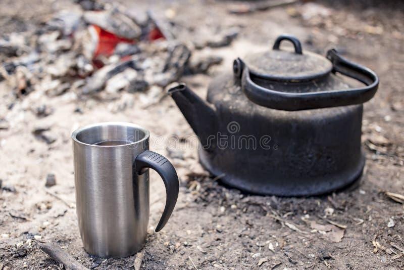 Schale mit einem heißen Getränk und ein Kesselstand aus den Grund durch das Feuer mit Glut, auf einem sonnigen Morgen im Lager lizenzfreie stockfotografie