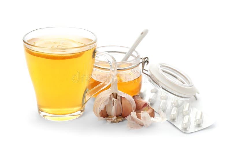 Schale mit heißem Tee, Honig, Knoblauch und Pillen lizenzfreie stockfotografie