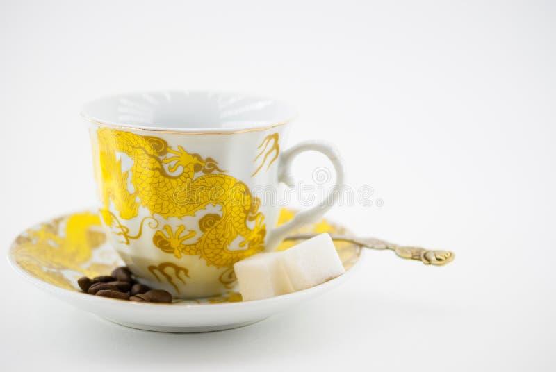 Schale mit Untertassen- und Löffelscheiben des Zuckers und der Kaffeebohnen lokalisiert auf weißem Hintergrund stockbilder