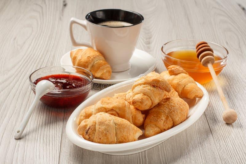 Schale schwarzer Kaffee mit Untertasse, frische Hörnchen auf weißem porce stockbilder