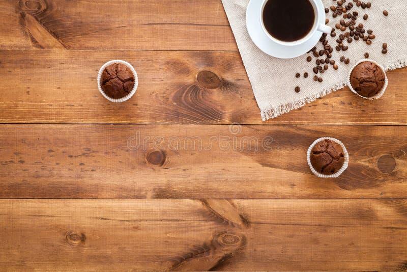 Schale schwarzer Kaffee, Muffins und coffe Bohnen herein zerstreut auf braunen Holztisch, cofee Cafécafeteria-Geschäftshintergrun lizenzfreie stockbilder
