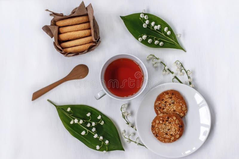 Schale schwarzer Tee in einem Kreis von Blumen des Maiglöckchens, des Hafers und des Mandelgebäcks auf weißem Hintergrund lizenzfreies stockfoto
