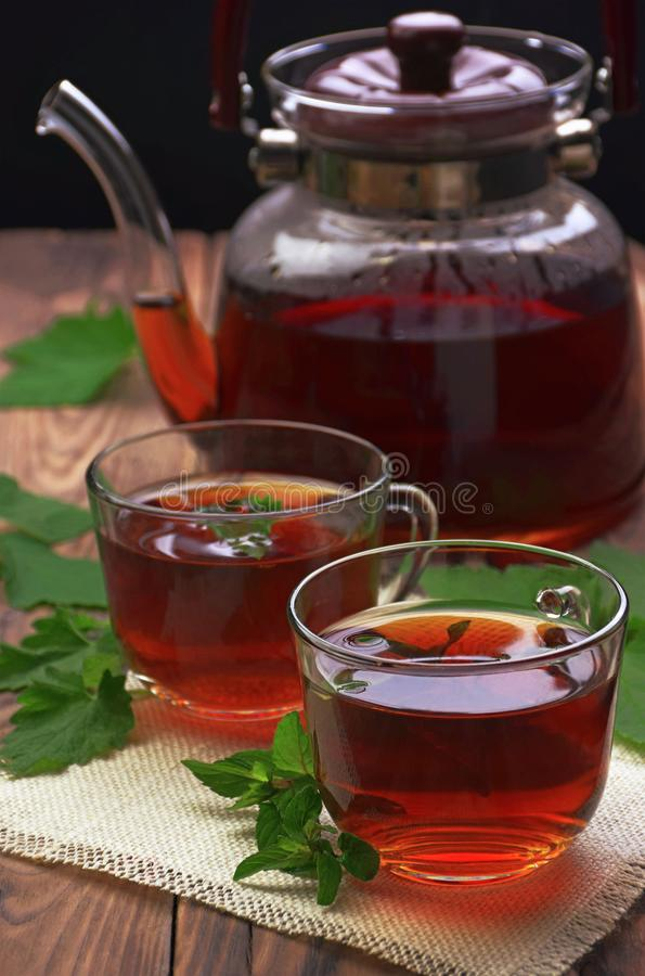 Schale tadelloser Tee und Blätter der Minze auf dem Tisch Eine Schale Kräutertee auf weißem Hintergrund Heilende Kräuter Eine Tas stockfoto