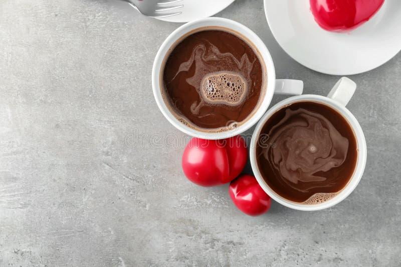 Schalen heiße Schokolade mit roten Herzen auf grauer Tabelle stockfoto