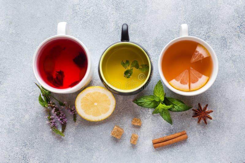 Schalen mit dem unterschiedlichen Tee rot, grün und schwarz auf grauer Tabelle Minze und Zitrone, brauner Zuckerzimt und Anis stockbild