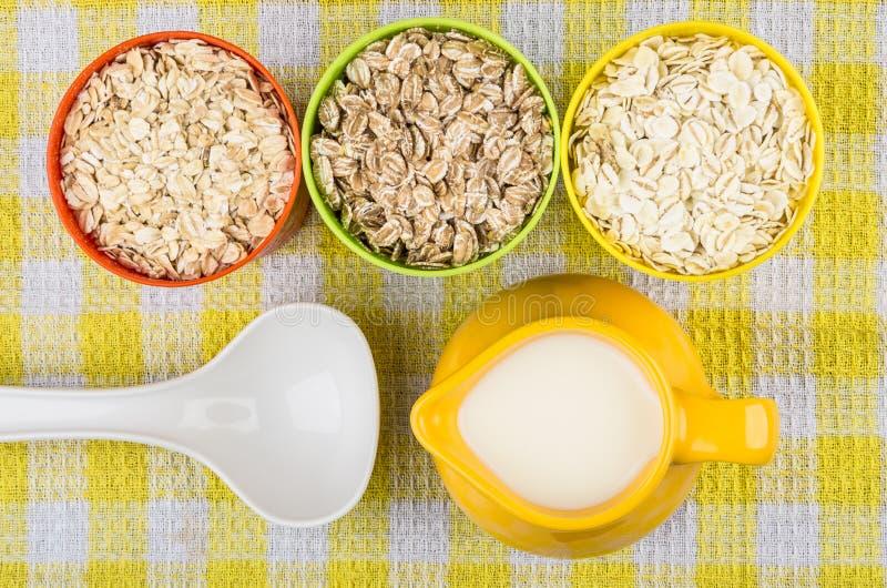 Schalen mit Hafer, Roggen, Gerstenflocken, Krugmilch und Löffel stockfoto