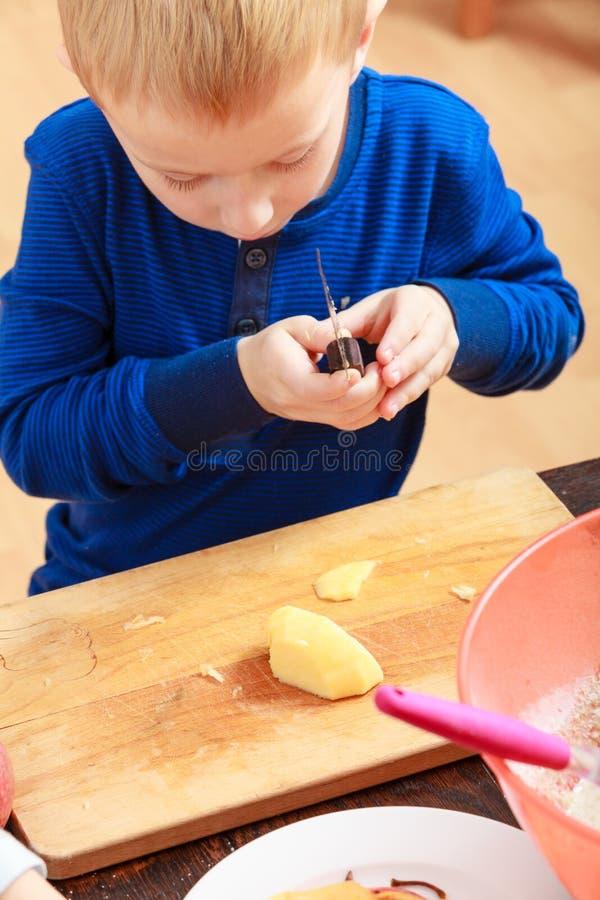 Schalen?pfel des kleinen Jungen mit Messer und dem Essen lizenzfreies stockbild