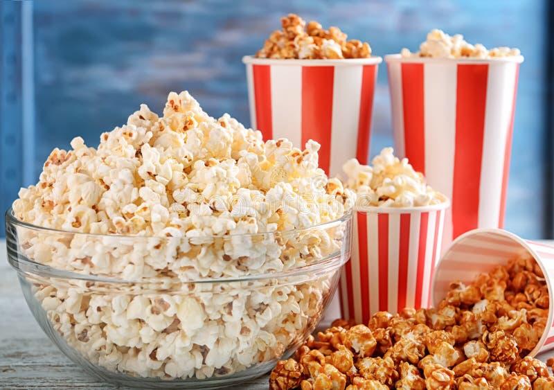 Schalen und Glasschüssel mit geschmackvollem Popcorn auf Holztisch lizenzfreie stockfotos