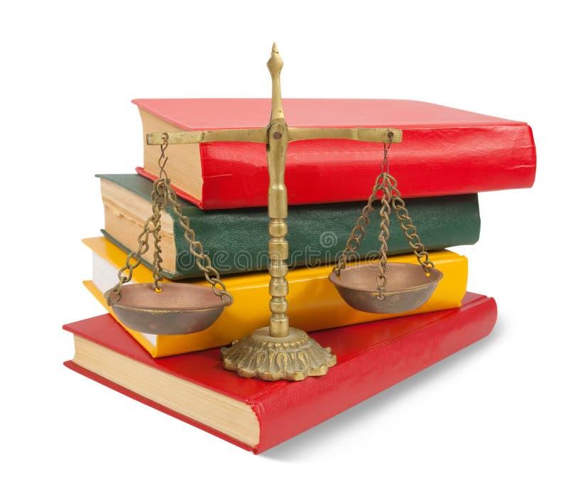 Schalen van rechtvaardigheid boven op wettelijke boeken over wit stock afbeeldingen
