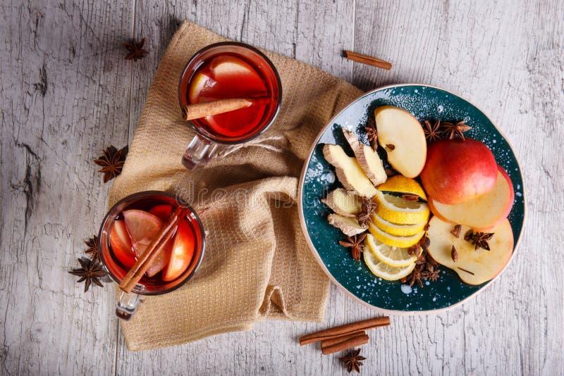 Schalen würziger roter Tee nahe bei einer Platte von geschnittenen Früchten auf einem Tabellenhintergrund Inländisches gesundes F lizenzfreies stockbild