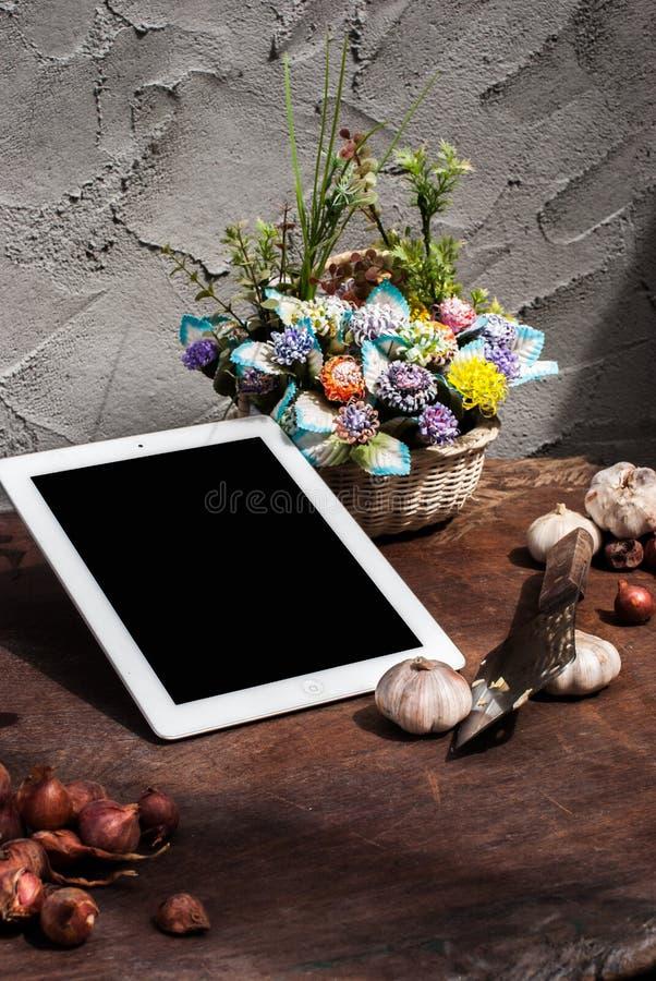 Schalottenlökar lök, vitlök, skärbräda, kniv, blomma med arkivfoto