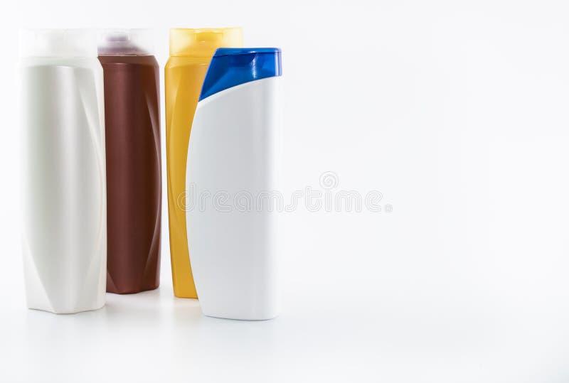 Schampo som fuktar flaskor i bruna, vita gula f?rger arkivfoto