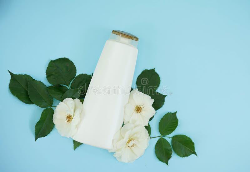 Schampoflaska på blå bakgrund med rosor för vita blommor, kopieringsutrymme, naturliga organiska skönhetsmedel, kroppomsorg royaltyfria foton