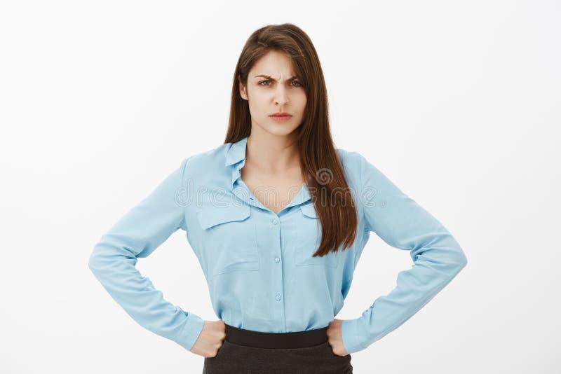 Schande voor ons bedrijf Handen op heupen houden en portret die van boze ontstemde bazige vrouw in blauwe blouse, fronsen royalty-vrije stock foto