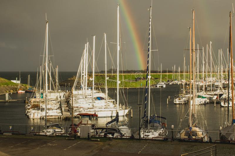 Scharendijke有彩虹的小船港口,荷兰看法  库存图片