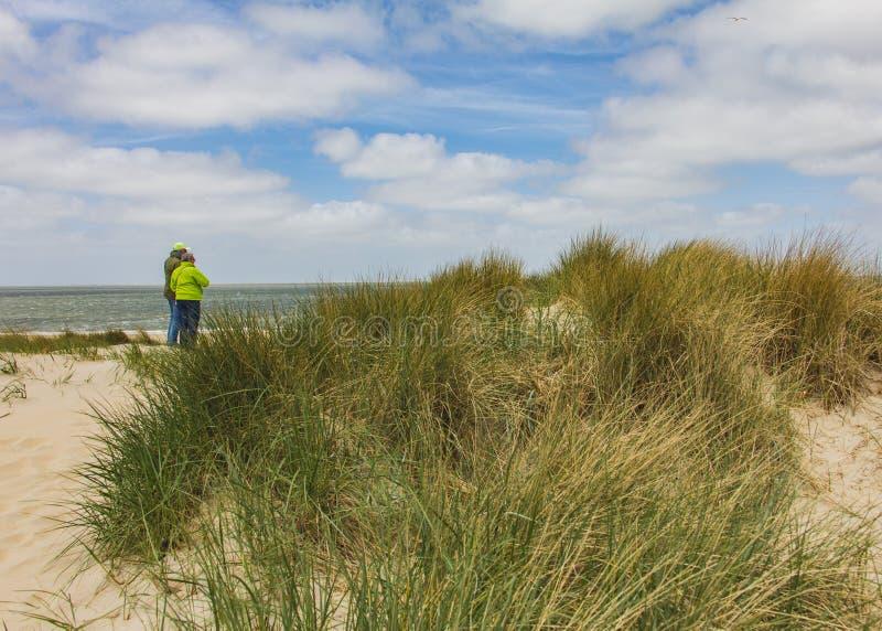 SCHARENDIJKE - PAÍSES BAJOS - MAYO, 17, 2018: pares mayores activos que miran el Norte-mar en dunas cerca de Países Bajos fotografía de archivo