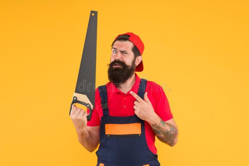 scharf und gefährlich Instandhaltung im Haus Er repariert alles Baumeister mit Säge Sägematte Mann lizenzfreie stockfotografie