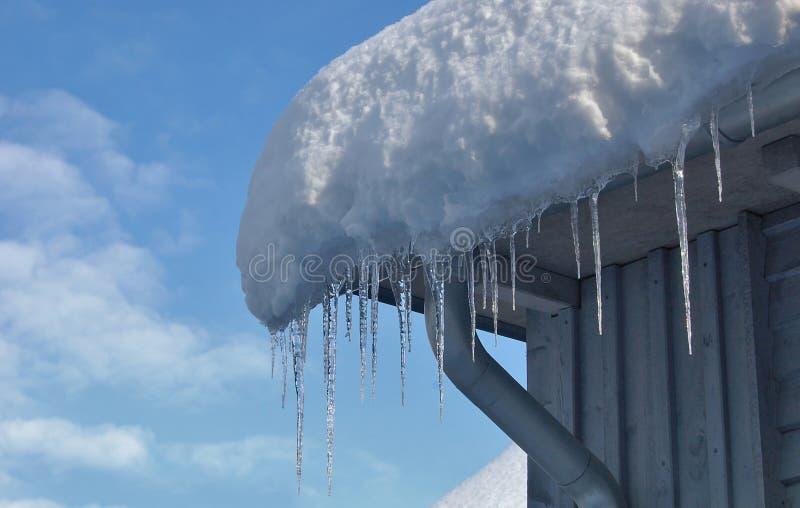 Scharfe helle Eiszapfen und geschmolzener Schnee, die von den Dachgesimsen des Dachs mit blauem Himmel im Hintergrund hängt stockfotos