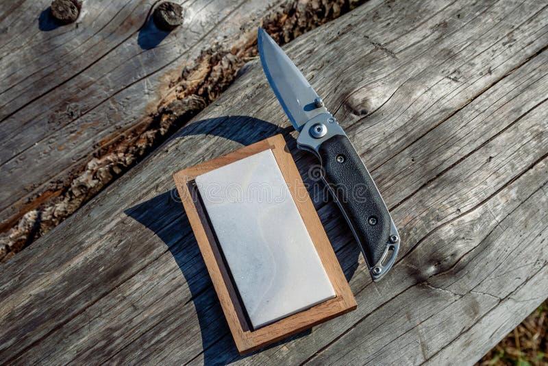 Scharfes Messer und Schleifstein auf einem hölzernen Hintergrund stockbild