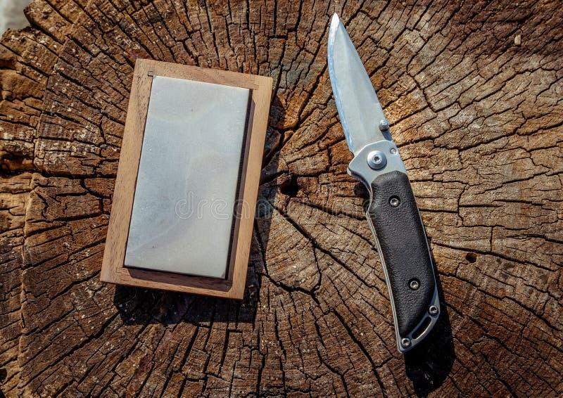 Scharfes Messer und Schleifstein auf einem hölzernen Hintergrund lizenzfreie stockbilder