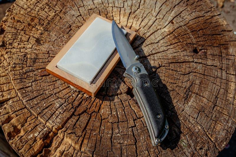 Scharfes Messer und Schleifstein auf einem hölzernen Hintergrund stockbilder