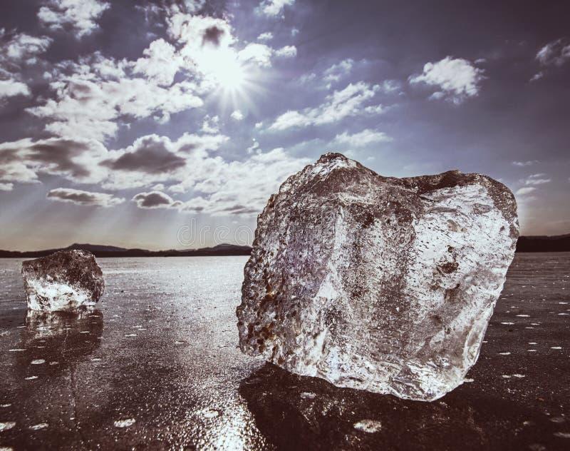 Scharfes Stück Eis Ein Symbol des harten Winters Die Strahlen der Sonne bilden Regenbogenschatten stockbild