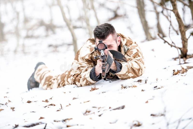 Scharfschütze, der durch Bereich zielt und mit Gewehr während der Operation - Kriegskonzept schießt oder Konzept jagt lizenzfreie stockbilder