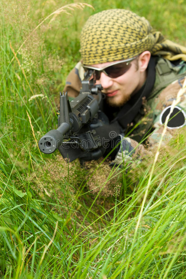 Scharfschütze, der in ein Gras legt stockfotos