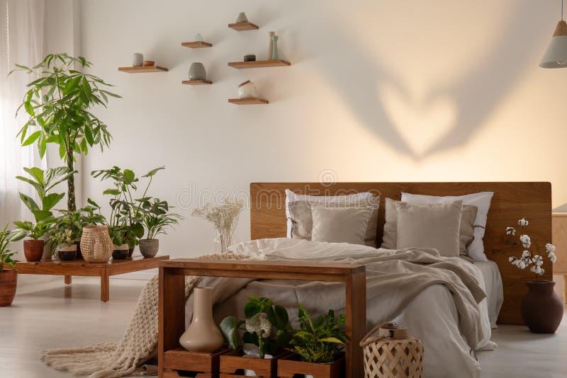 Schatten auf der Wand hinter Bett mit hölzerner Kopfende im Schlafzimmerinnenraum mit Anlagen Reales Foto lizenzfreie stockfotos