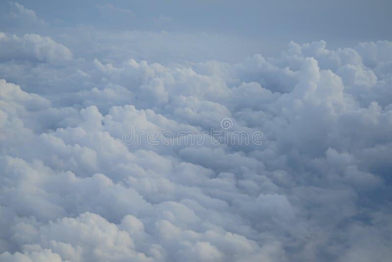 Schatten des hellblauen Farbhimmels und der sich hin- und herbewegenden weißen Wolkenmärchenlandansicht vom Flugzeugfenster stockfotografie