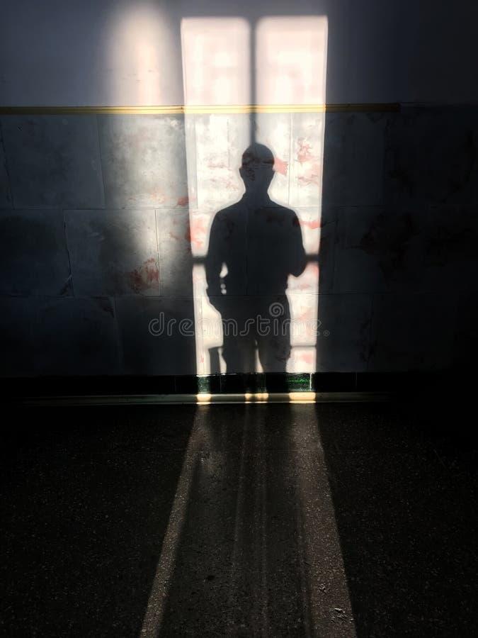 Schatten des stehenden Mannes auf der Wand stockfoto