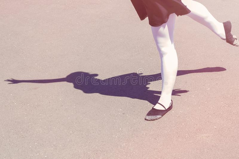 Schatten des Tänzermädchens, das Tanzmaßnahmen in einem Badeanzug für Tanzen und Ballettschuhe trifft stockbild