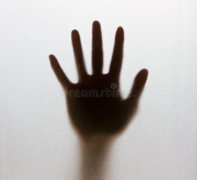 Schatten einer undeutlichen Hand hinter dem bereiften Glas lizenzfreie stockbilder