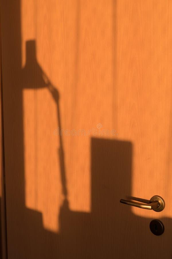 Schatten eines lemp auf einer Holztür lizenzfreie stockfotos