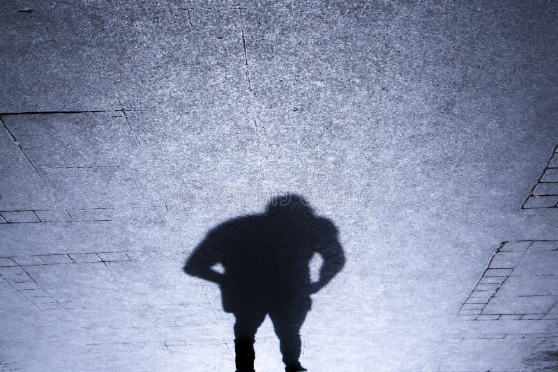 Schatten eines Mannes, der auf patterened Bürgersteig steht stockfoto