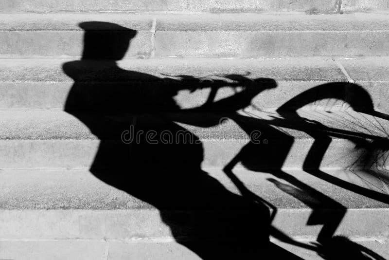 Schatten eines Radfahrers, der sein Fahrrad herauf die Treppe drückt lizenzfreie stockfotos