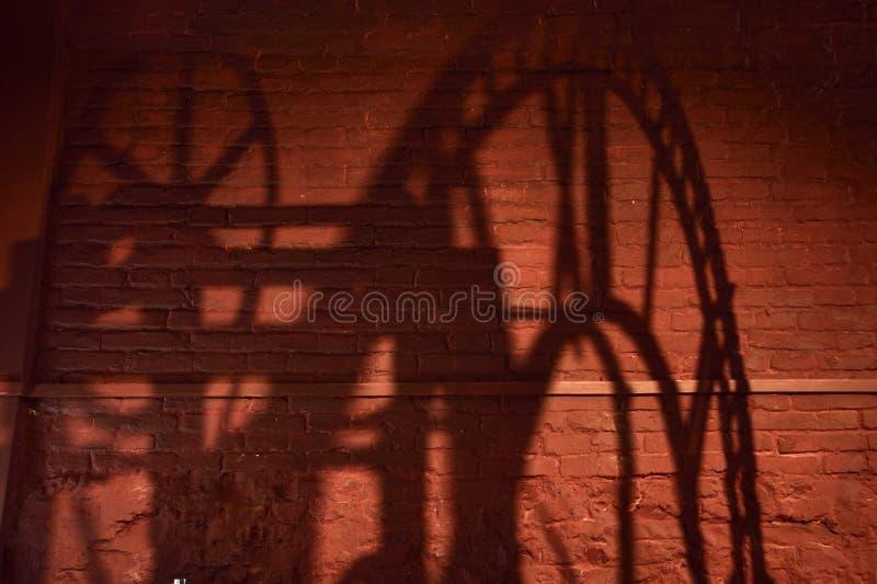 Schatten eines Uhrmechanismus mit römischen Ziffern auf einer Backsteinmauer stockfotos