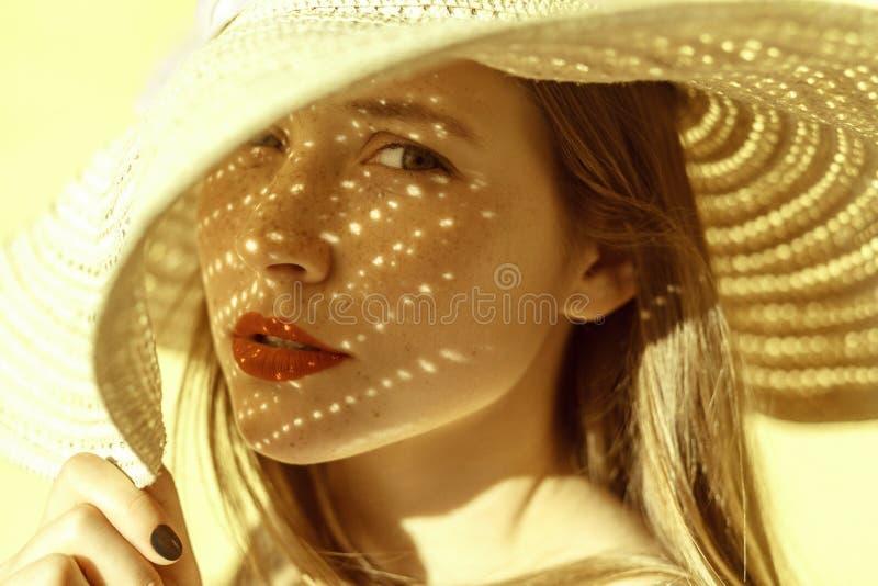 Schatten fällt auf eine Frau von einem Hut stockbild