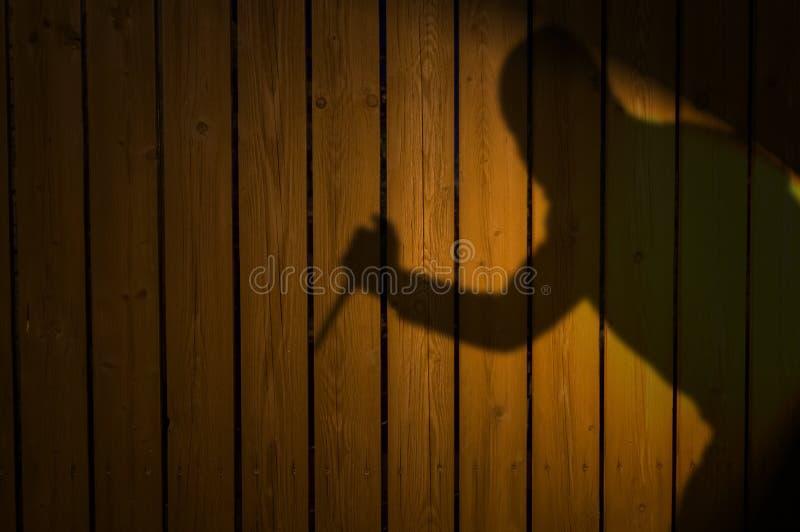Schatten oder Schattenbild des Verbrechers mit Messer auf Zaun lizenzfreie stockbilder