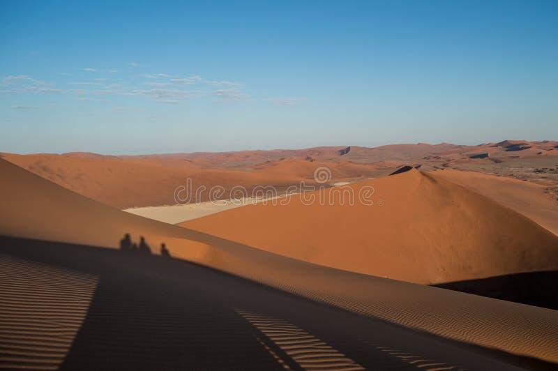 """Schatten von drei Leute †""""kletternder Big Daddy Dune bei Sonnenaufgang lizenzfreie stockbilder"""