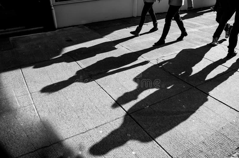Schatten von vier gehenden Fußgängern lizenzfreie stockfotografie
