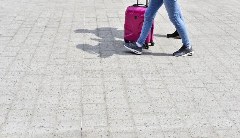 Schatten von zwei Reisenden, die mit einem rosa Koffer gehen stockbild