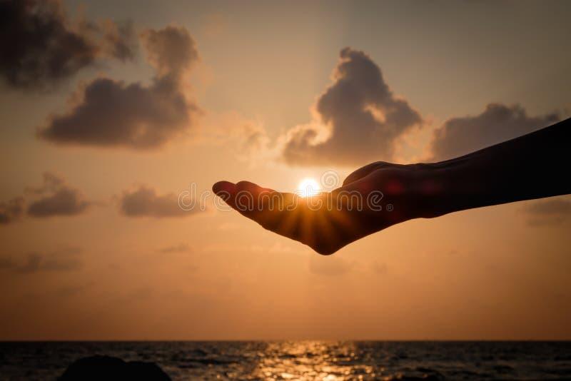 Schattenbild übergibt das Fangen der fallenden Sonne lizenzfreies stockbild