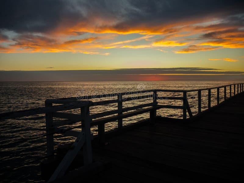 Schattenbild der Anlegestelle mit dem schönen Sonnenuntergang und dem bewölkten Himmel in dem Ozean in Henley Beach, Adelaide, Sü lizenzfreie stockbilder