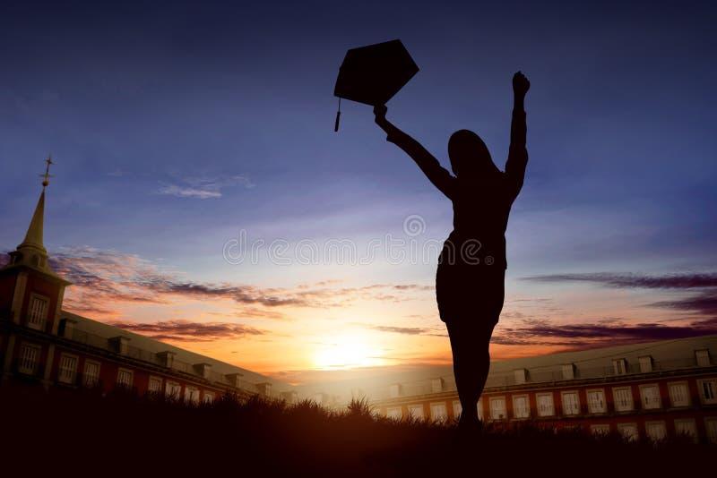 Schattenbild der aufgeregten Frau mit Staffelungshut Absolventen feiernd lizenzfreie stockfotografie